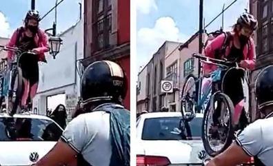 Una ciclista pasa por encima de un coche por aparcar en el carril bici